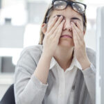A woman at her computer rubbing her eyes