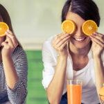 Happy women holding orange slices over their eyes