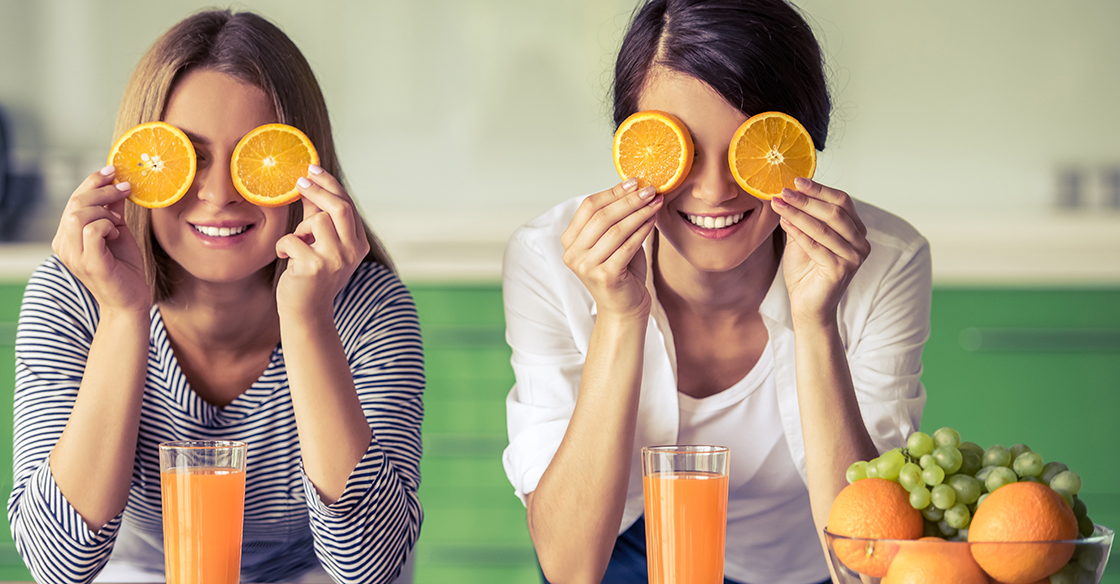 Happy women holding orange slices over their eyes