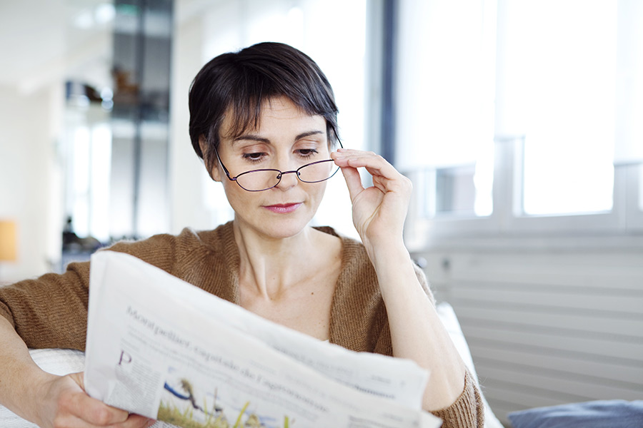 Woman with presbyopia reading a newspaper