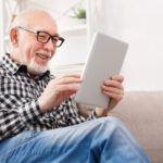 Man wearing progressive eye glasses looking at a tablet