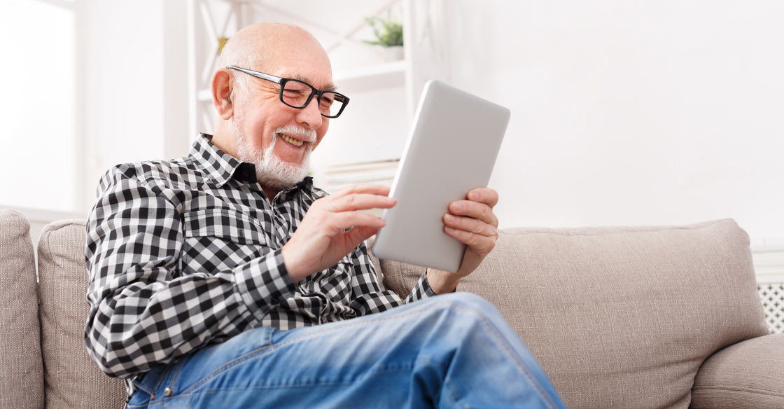 Man wearing progressive eye glasses looking at a tablet