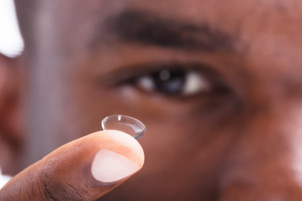Man holding contact lens on finger