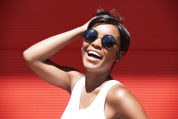 Happy woman wearing sunglasses in front of red wall